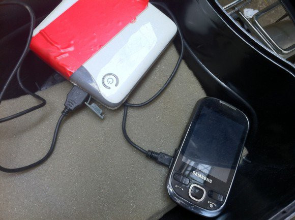 The phone plugged to a portable battery charger
